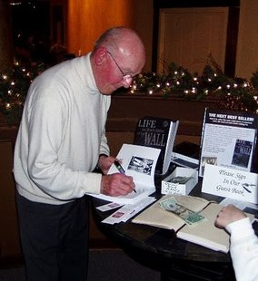 "World War Two survivor Gunther Skaletz signs a copy of his book ""Life on Both Sides of the Wall"""