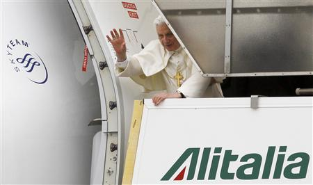 Pope Benedict XVI waves from the platform at the top of the stairs before boarding his plane to Portugal at Fiumicino international airport in Rome, May 11, 2010. REUTERS/Alessandro Bianchi