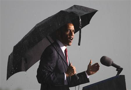 U.S. President Barack Obama speaks in the pouring rain during a Memorial Day event at the Abraham Lincoln National Cemetery in Elwood, Illinois, May 31, 2010. REUTERS/Larry Downing