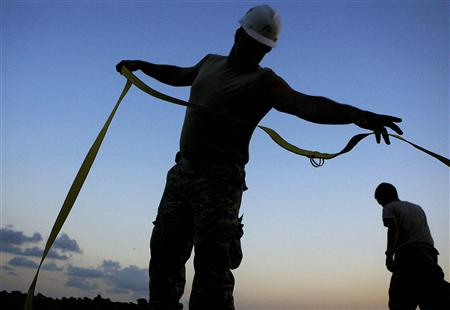 Louisiana National Guardsmen unravel support straps far a Tiger Dam, to protect the Grand Isle from encroaching oil coming in with the high tide in Grand Isle, Louisiana May 31, 2010. REUTERS/Sean Gardner