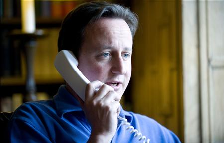 Britain's Prime Minister David Cameron talks to U.S. President Barack Obama on the phone in his office at his official country residence of Chequers outside London June 12, 2010. REUTERS/Andrew Parsons/handout
