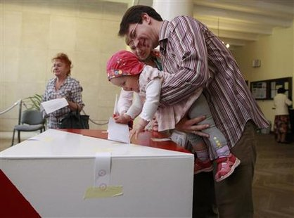 A man holds a child, while casting his vote at a polling station in Warsaw during presidential elections June 20, 2010. REUTERS/Peter Andrews