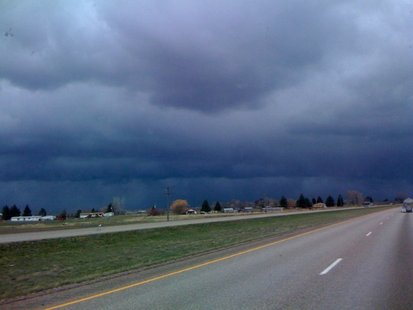 Storm clouds gather along a rural stretch of highway.