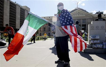 A protester with a U.S. flag and a Mexican flag stands outside the Arizona State Capitol in Phoenix, Arizona April 23, 2010 in protest of an immigration law signed by Arizona Governor Jan Brewer. REUTERS/Laura Segall