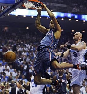 Charlotte Bobcats center Tyson Chandler (L) dunks in front of Orlando Magic center Marcin Gortat (R) during the first half of Game 2 of their NBA Eastern Conference playoff series in Orlando, Florida April 21, 2010. REUTERS/Kevin Kolczynski