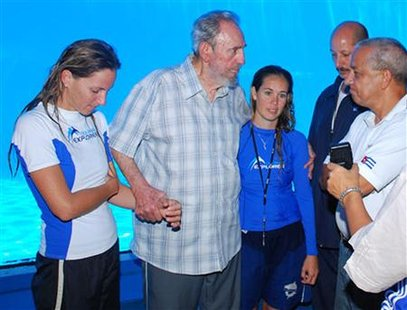 Former Cuban leader Fidel Castro (2nd L) stands with trainers of Havana's National Aquarium during a visit July 15, 2010. Castro has been seen only in occasional photographs and videos since he underwent emergency intestinal surgery in July 2006 and ceded power provisionally to his younger brother, Raul Castro. He resigned in February 2008 and Raul Castro was officially elected president by the National Assembly. REUTERS/Revolution Studios