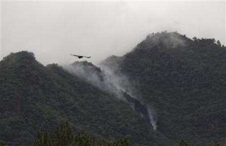 Smoke rises from the wreckage of a passenger plane which has crashed in The Margalla Hills on the outskirts of Islamabad, July 28, 2010. 