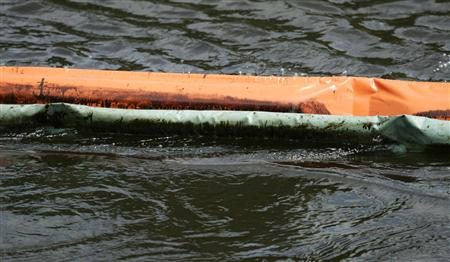 Booms are seen floating on the Kalamazoo river, after an oil pipeline, owned by Enbridge Energy Partners, leaked an estimated 820,000 gallons of oil into the Kalamazoo river in Western Michigan near Marshall July 30, 2010. REUTES/Rebecca Cook