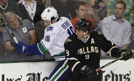 The crowd reacts as Dallas Stars' Mike Modano (R) pushes Vancouver Canucks' Steve Bernier into the boards during second period play in their NHL hockey game in Dallas, Texas March 24, 2009. REUTERS/Jessica Rinaldi