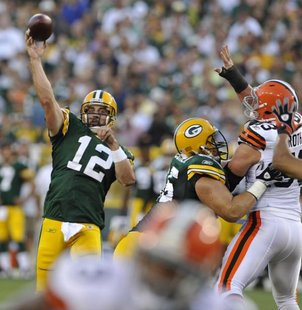 Green Bay Packers' Aaron Rodgers (12) tosses a touchdown pass against the Cleveland Browns during the first half of a preseason NFL football game Saturday, Aug. 14, 2010, in Green Bay, Wis. (AP Photo/Jim Prisching)