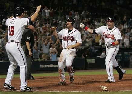 Atlanta Braves runner Brooks Conrad (C) celebrates as he scores the winning run against the Los Angeles Dodgers and is greeted by teammates Brandon Hicks (L) and Eric Hinske (R) in the bottom of the ninth inning of MLB National League action in Atlanta, Georgia August 16, 2010. REUTERS/Tami Chappell
