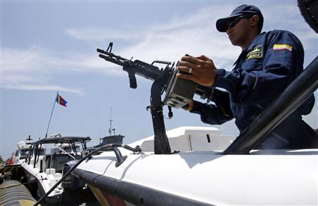 A Colombian navy sailor stands guard inside a patrol boat during a media visit to the navy base in Cartagena in this August 27, 2009 file photo. REUTERS/Jairo Castilla/Files