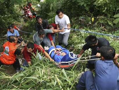 Rescuers carry an injured passenger of a bus that fell into a ravine in Sablan, Benguet in northern Philippines August 18, 2010. 41 people were killed after a bus lost control and fell into a 50-meter ravine in the northern province of Benguet on Wednesday, local officials said. REUTERS/Harley Palangchiao