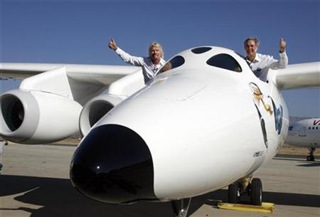 Virgin Group's Founder billionaire Richard Branson (L) and Burt Rutan, president of Scaled Composites, wave from the window of Virgin Galactic's mothership WhiteKnightTwo during its public roll-out in Mojave, California July 28, 2008. REUTERS/Fred Prouser