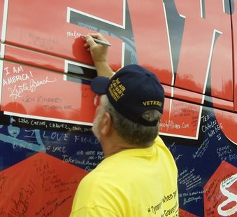 "Erv Thums, a Vietnam veteran from Wausau, signs a message protesting out-of-control government spending on the side of a ""Spending Revolt"" bus during a rally Tuesday in Rib Mountain."