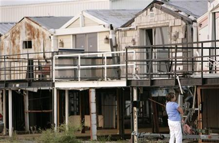 A woman looks at homes damaged by Hurricane Katrina in a marina on Lake Pontchartrain in New Orleans, Louisiana, August 25, 2007. REUTERS/Lee Celano