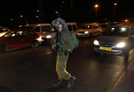 An Israeli soldier patrols along a highway near the site of a shooting attack which killed four Israelis near the West Bank settlement of Kiryat Arba, near Hebron, August 31, 2010. REUTERS/Ronen Zvulun