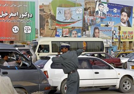An Afghan traffic policeman directs traffic on a busy road adorned with pictures of candidates taking part in the forthcoming parliamentary elections in Kabul September 15, 2010. REUTERS/Fayaz Kabli