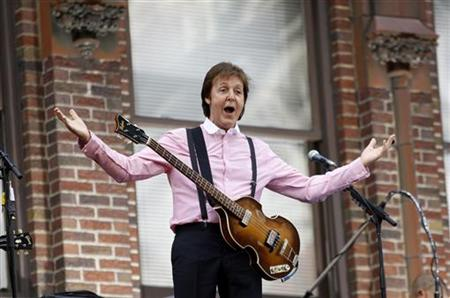 Paul McCartney responds to cheers in Midtown Manhattan as he comes out to play a concert with his band atop the marquee of the Ed Sullivan Theater, July 15, 2009. REUTERS/Mike Segar