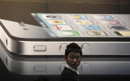 A man stands next to a giant advertisement for an iPhone 4 displayed at a shop in Bangkok September 24, 2010. REUTERS/Chaiwat Subprasom
