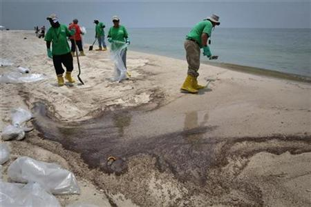 Contract workers shovel oil from a beach impacted by the Deepwater Horizon oil spill in Gulf Shores, Alabama June 16, 2010. REUTERS/Lee Celano