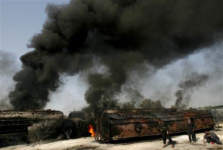 Police collect bullets shells next to burning oil tankers on a highway near Shikarpur, about 39 km (24 miles) from Sukkur in Pakistan's Sindh province, October, 1, 2010. Suspected militants in Pakistan set fire to tankers carrying fuel for NATO troops in Afghanistan on Friday, officials said, a day after three soldiers were killed in a cross-border NATO air strike. REUTERS/Athar Hussain