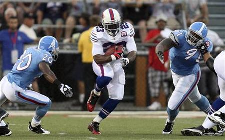 Buffalo Bills' Marshawn Lynch runs between Tennessee Titans defenders Nick Harper (20) and Jason Jones (R) in the first quarter of their AFC-NFC Hall of Fame Game in Canton, Ohio August 9, 2009. REUTERS/Aaron Josefczyk