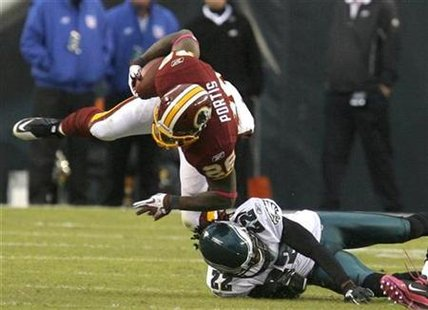 Washington Redskins running back Clinton Portis is tackled by the Philadelphia Eagles Asante Samuel (22) during the third quarter of their NFL game in Philadelphia, Pennsylvania, October 3, 2010. REUTERS/Tim Shaffer
