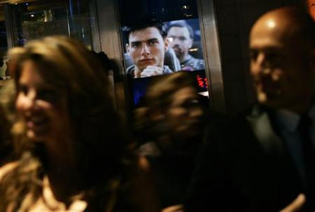 "An image of Tom Cruise from the movie ""Top Gun"" is reflected in a window as people arrive at the Museum of the Moving Image Salute to Tom Cruise in New York November 6, 2007. REUTERS/Shannon Stapleton"