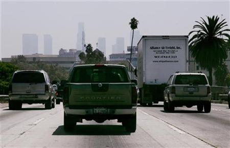 Cars and trucks travel on a freeway in Los Angeles, California August 31, 2006 with the skyline of Los Angeles barely visible in background. REUTERS/Fred Prouser