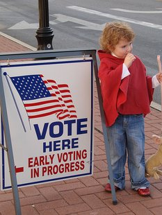 A young child stands in front of a sign directing voters where to cast ballots