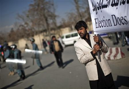 A supporter of Afghan candidates for the parliamentary elections holds a banner during a protest in Kabul November 24, 2010. Afghan election candidates took to the streets of Kabul on Wednesday to protest against a polling process they say was corrupt and shameful ahead of the expected announcement of final results from the Sept. 18 vote. REUTERS/Ahmad Masood