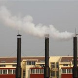 Smoke billows from chimneys of a heating plant near a residential compound in Beijing in this November 23, 2010 file photo. REUTERS/Petar Kujundzic