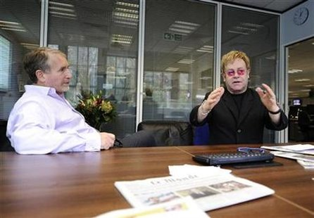 Elton John (R) chats with Simon Kelner, editor of The Independent newspaper at their editorial offices in London November 30, 2010. John is the guest editor of the special World Aids Day edition of the British daily paper due out on Wednesday. REUTERS/Dylan Martinez