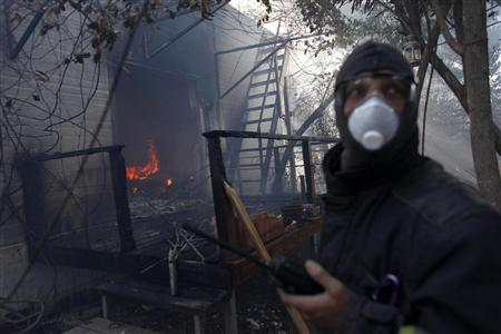 A fire fighter tries to save a burning house after a forest fire hit the area of Ein Hod, near the northern city of Haifa December 4, 2010. REUTERS/Nir Elias