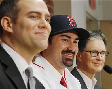 Boston Red Sox general manager Theo Epstein (L) and principal owner John Henry (R) introduce newly acquired Red Sox player Adrian Gonzalez at a news conference at Fenway Park in Boston, Massachusetts December 6, 2010. REUTERS/Brian Snyder