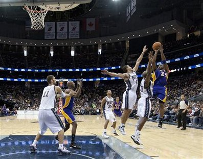 Los Angeles Lakers guard Kobe Bryant (24) shoots for three points over New Jersey Nets forward Kris Humphries (43) and forward Quinton Ross (13) in the fourth quarter of their NBA basketball game in Newark, New Jersey, December 12, 2010. REUTERS/Ray Stubblebine