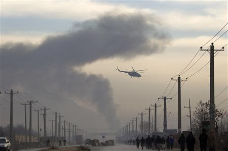 A helicopter flies as smoke billows from a suicide attack in Kabul December 19, 2010. REUTERS/Ahmad Masood