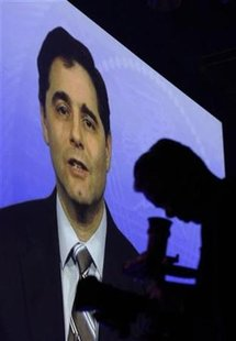 A videographer is silhouetted in front of a video presentation featuring Federal Communications Commission (FCC) Chairman Julius Genachowski during the International CTIA Wireless trade show in Las Vegas, Nevada March 23, 2010. REUTERS/Steve Marcus