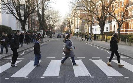 Pedestrians cross the road outside the Abbey Road Studios, in north London February 17, 2010. REUTERS/Jas Lehal