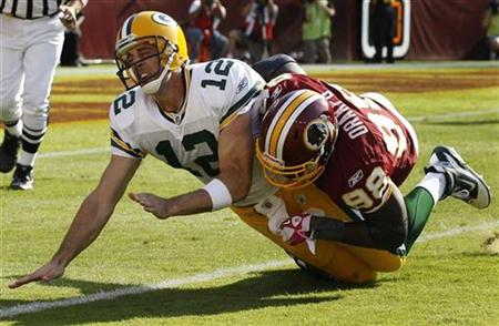 Green Bay Packers quarterback Aaron Rodgers is hit by Washington Redskins Brian Orakpo after throwing the ball in the second half of their NFL game in Landover, Maryland, October 10, 2010. REUTERS/Larry Downing