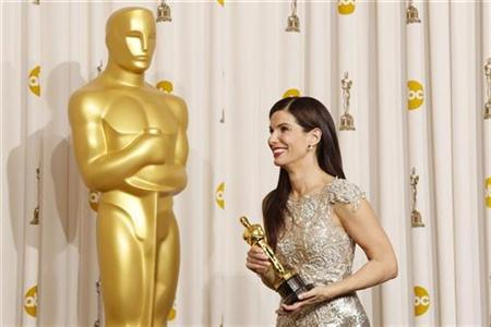 "Sandra Bullock smiles with her best actress Oscar after winning for her role in ""The Blind Side"" backstage at the 82nd Academy Awards in Hollywood March 7, 2010. REUTERS/Lucy Nicholson"