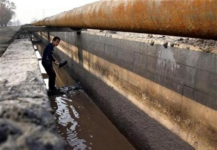 A worker shovels cast-off tailings out of a channel underneath a pipeline that transports crushed mineral ore containing rare earths to a disposal dam near Xinguang Village, located on the outskirts of the city of Baotou in China's Inner Mongolia Autonomous Region in this October 31, 2010 picture. REUTERS/David Gray