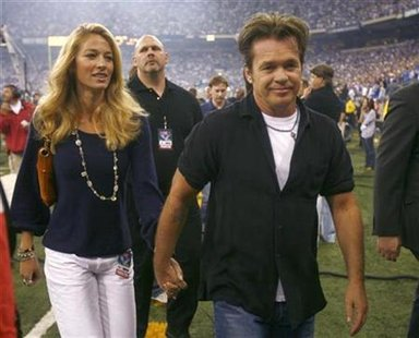 Musician John Mellencamp (R) walks hand in hand with his wife, Elaine-Irwin Mellencamp, after performing prior to the start of the Indianapolis Colts and New Orleans Saints' NFL football game in Indianapolis September 6, 2007. REUTERS/Brent Smith