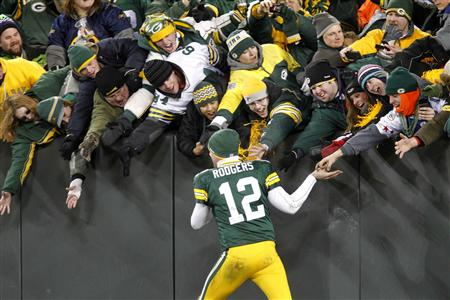 Green Bay Packers starting quarter back Aaron Rodgers celebrates victory against the Chicago Bears with fans in their NFL football game in Green Bay, Wisconsin January 2, 2011. REUTERS/Jeffrey Phelps