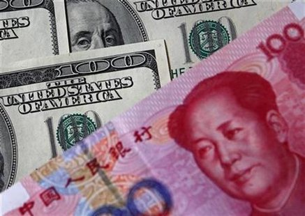 A 100 yuan banknote (bottom) is placed next to U.S. $100 banknotes in this picture illustration taken in Beijing in this November 1, 2010 file photo. REUTERS/Petar Kujundzic