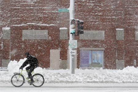 A man travels on his bicycle during a winter nor'easter snow storm in Boston, Massachusetts January 12, 2011. REUTERS/Brian Snyder