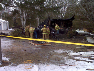 Firefighters investigate the scene of a fire in the Marinette County Town of Lake, Jan. 12, 2011. (courtesy of FOX 11).