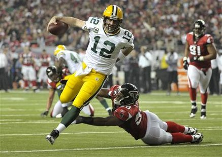 Green Bay Packers quarterback Aaron Rodgers (12) runs into the end zone past Atlanta Falcons linebacker Curtis Lofton for a touchdown in the 3rd quarter during their NFC Divisional NFL playoff football game in Atlanta January 15, 2011. REUTERS/Rich Addicks
