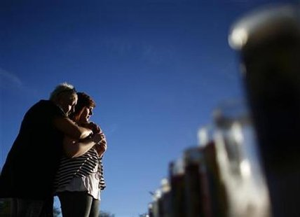 Ivonne Gaitan (L) and Miciela Sahner embrace at a memorial for U.S. congresswoman Gabrielle Giffords and other victims at University Medical Center in Tucson, Arizona January 17, 2011. REUTERS/Eric Thayer